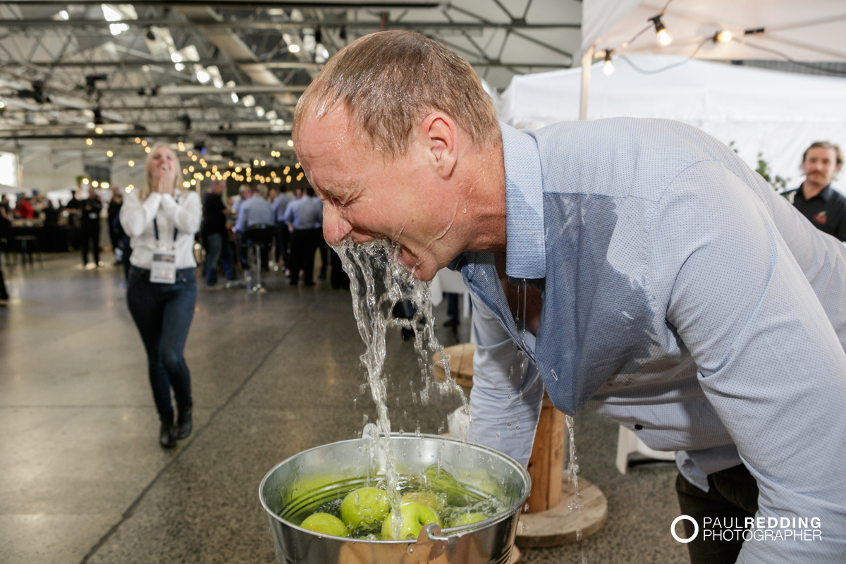 44- Rob Carlton Bobbing for apples at Lark Distillery stand at Insurance Advisernet Australia Conference 2015 - Trade Show at Princes Wharf No 1 Shed. Photography by Paul Redding, Hobart Trade Show Photography.
