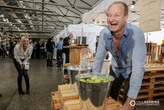 42- Rob Carlton bobbing for apples at Lark Distillery stand at Insurance Advisernet Australia Conference 2015 - Trade Show at Princes Wharf No 1 Shed. Photography by Paul Redding, Hobart Trade Show Photographer.